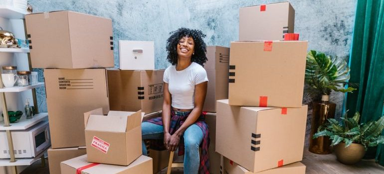 girl surrounded by moving boxes, waiting for moving services NH