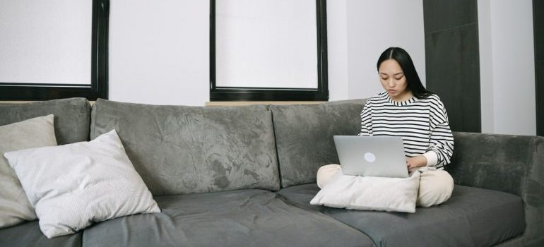 A woman sitting on a couch looking at her laptop